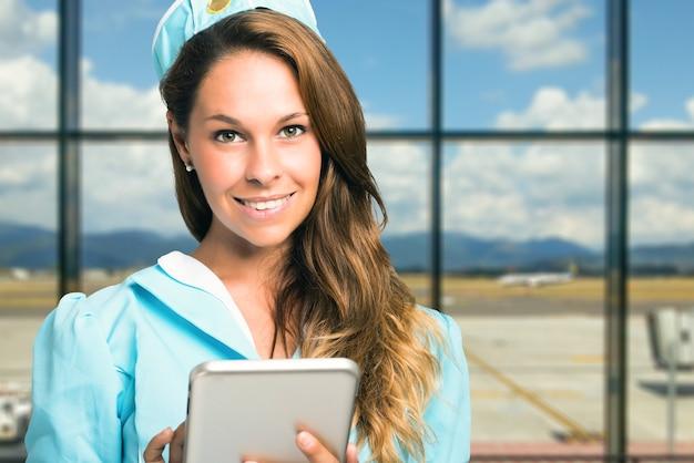 Glimlachende stewardess die een digitale tablet gebruikt