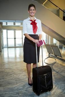 Glimlachende stewardess met instapkaart en trolleytas op luchthaventerminal