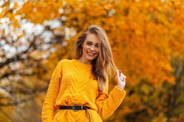 Glimlachende stijlvolle gelukkige vrouw met zoete glimlach in vintage gebreide trui loopt in het herfstpark met gouden herfstbladeren