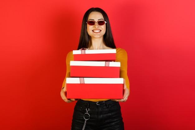 Glimlachende stijlvolle jonge vrouw in rode zonnebril stapel geschenken houden en permanent op rode achtergrond.