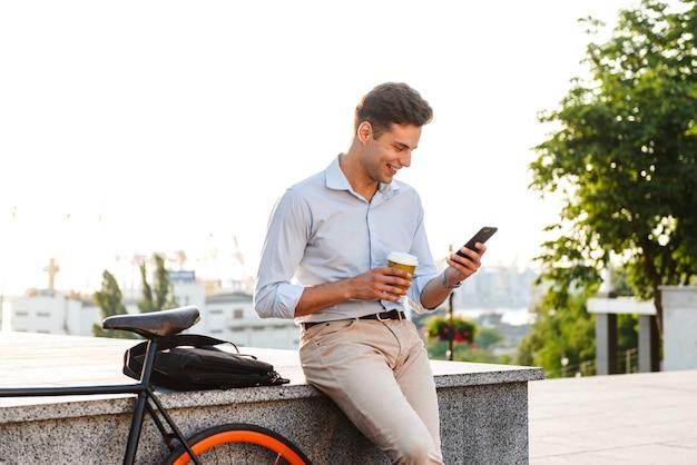 Glimlachende stijlvolle jongeman met behulp van mobiele telefoon