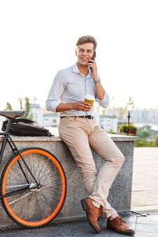 Glimlachende stijlvolle jongeman praten op mobiele telefoon
