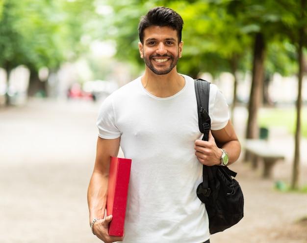 Glimlachende student buiten op de binnenplaats van een universiteit