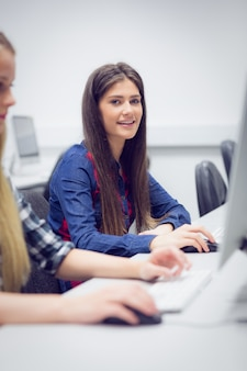Glimlachende student die aan computer bij universiteit werkt
