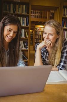 Glimlachende student die bij bibliotheek aan universiteit werkt