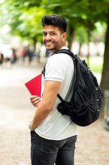 Glimlachende student die buiten op de binnenplaats van een universiteit loopt