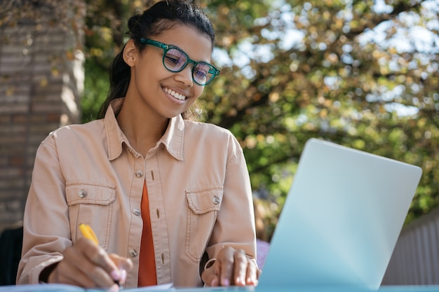 Glimlachende student die laptop computer gebruikt, online studeert, taal leert, examenvoorbereiding