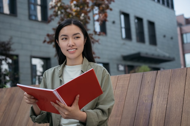 Glimlachende student die studeert met boekexamenvoorbereiding op de universiteitscampus onderwijsconcept