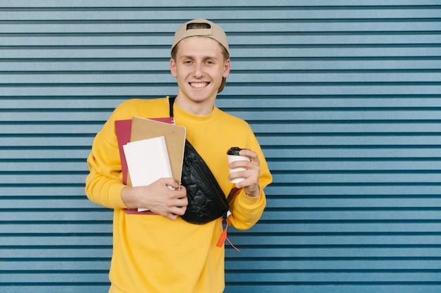 Glimlachende student in een geel sweatshirt en pet staat