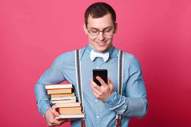 Glimlachende student met stapel boeken, gekleed overhemd in één toon, bretels en vlinderdas