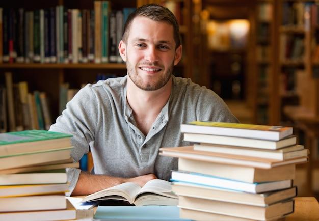 Glimlachende student omringd door boeken