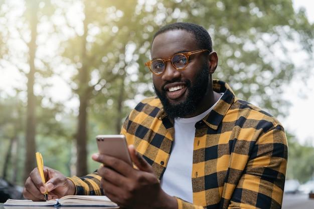 Glimlachende student studeert, leert taal, onderwijsconcept. zelfverzekerde afrikaanse man met behulp van mobiele telefoon, notities maken, freelance project online werken