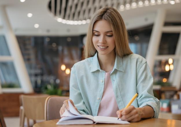 Glimlachende student studeert, notities maken, lezen, onderwijsconcept