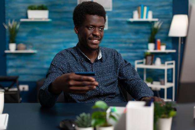 Glimlachende student zit aan bureau in woonkamer met creditcard