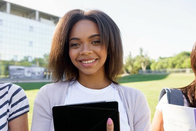 Glimlachende studenten afrikaanse vrouw die zich in openlucht bevindt