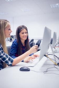 Glimlachende studenten die aan computer bij universiteit werken