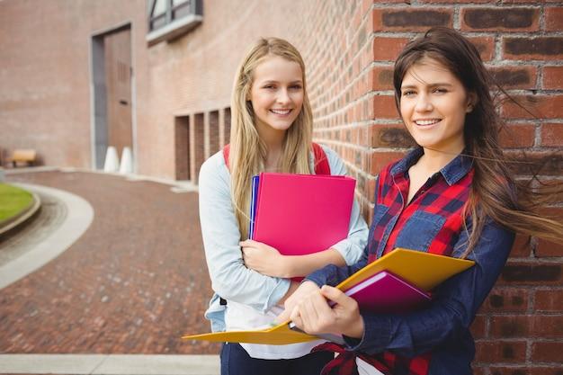 Glimlachende studenten die boek lezen op universiteit