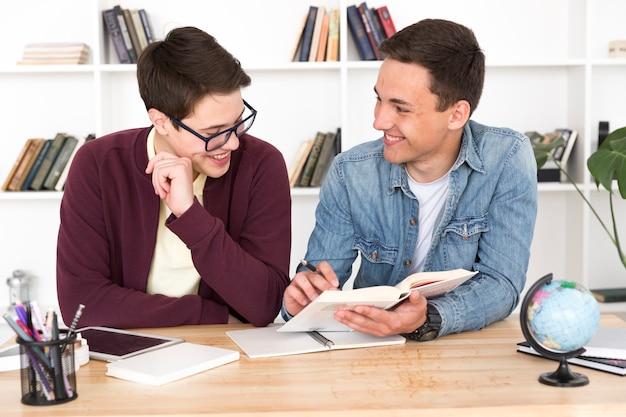 Glimlachende studenten die boek lezen