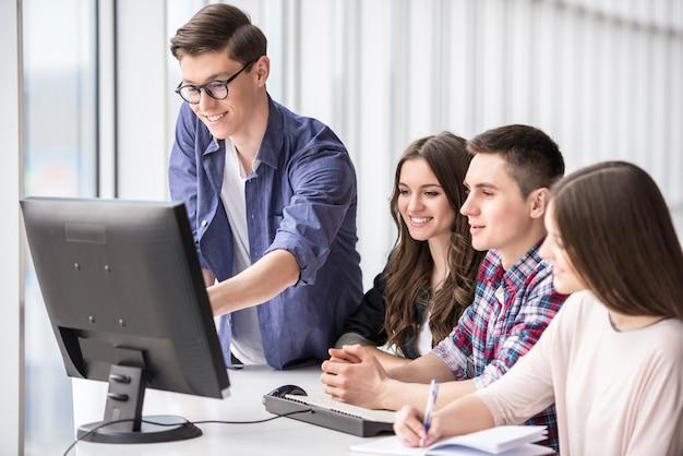 Glimlachende studenten die computerpc aan universiteit bekijken.