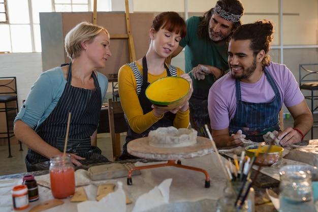 Glimlachende studenten die leraar het schilderen pot bekijken