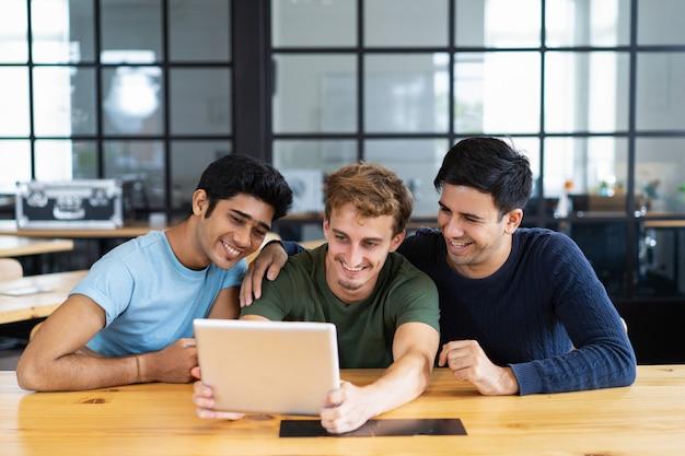 Glimlachende studenten die media-inhoud bekijken of een video-oproep hebben