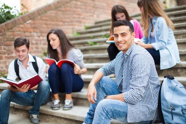 Glimlachende studenten die op een trap zitten