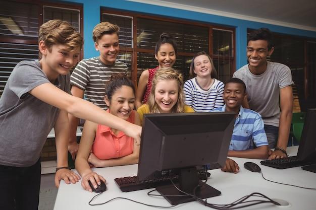 Glimlachende studenten die samen in computerlokaal studeren