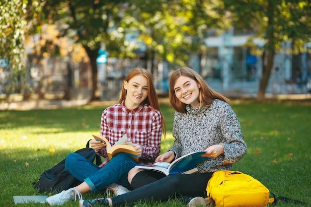 Glimlachende studenten die zitting op gras stellen