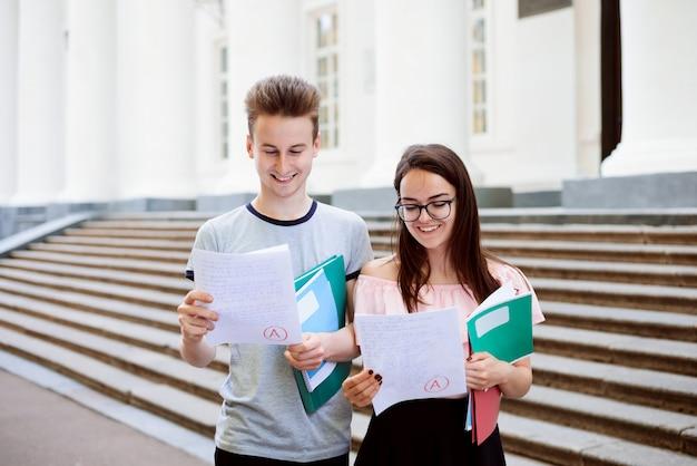 Glimlachende studenten met testresultaten in de buurt van het universiteitsgebouw