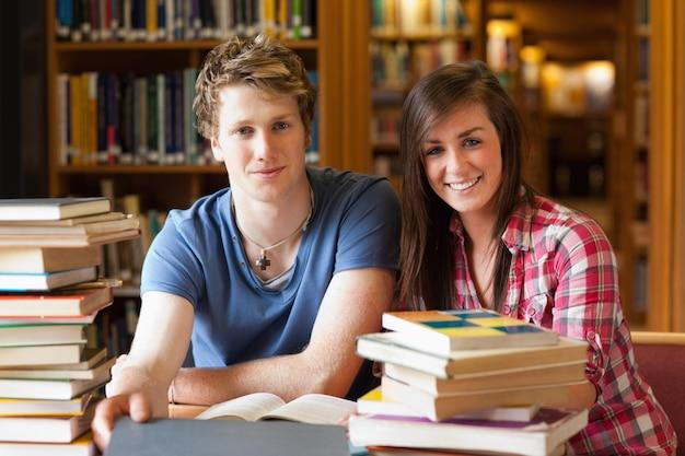 Glimlachende studenten omringd door boeken