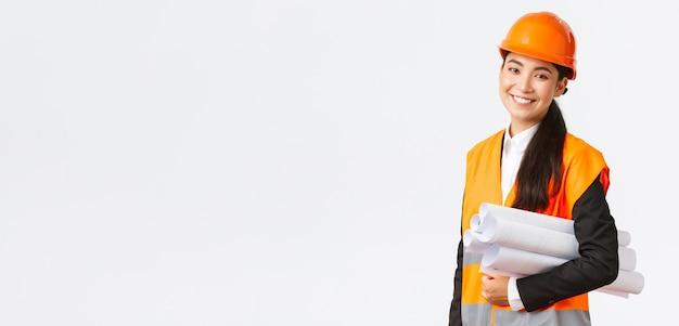 Glimlachende succesvolle aziatische vrouwelijke architect, bouwingenieur in veiligheidshelm, blauwdrukken dragen en gelukkig glimlachen naar de camera, bouwproject introduceren, staande witte achtergrond