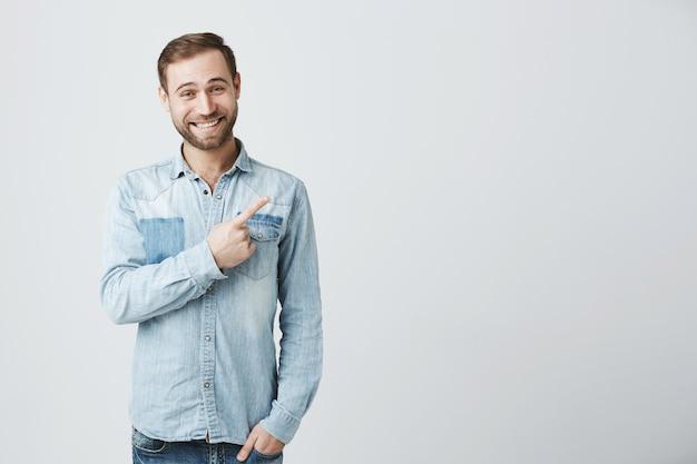 Glimlachende succesvolle mens die tevreden vinger hoogste rechterbovenhoek richten