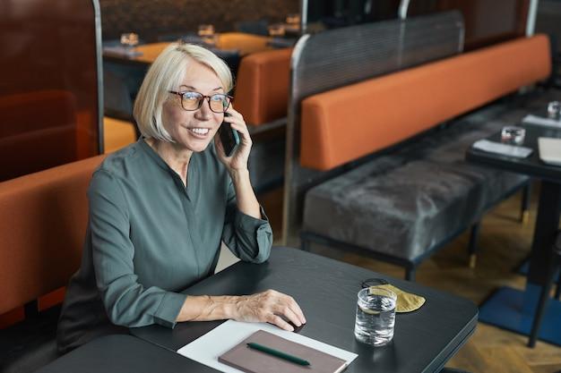 Glimlachende succesvolle volwassen zakenvrouw in brillen en grijs shirt zittend aan tafel met organisator en telefonisch communiceren in restaurant