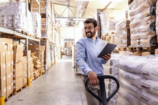 Glimlachende supervisor die vorkheftruck duwt en tablet vasthoudt om goederen voor uitvoer te controleren.