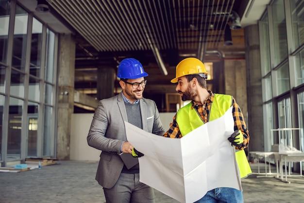 Glimlachende supervisor in gesprek met bouwvakker over bouwwerkzaamheden. werknemer blauwdrukken te houden en uit te leggen aan supervisor.
