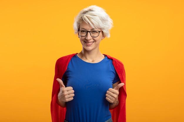 Glimlachende supervrouw met rode cape in optische glazen duimen omhoog van twee handen die op oranje muur worden geïsoleerd