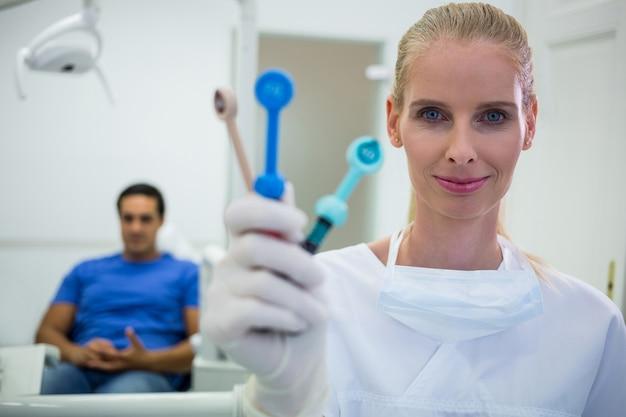 Glimlachende tandarts die tandhulpmiddelen houdt