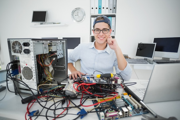 Glimlachende technicus die aan gebroken computer in zijn bureau werkt