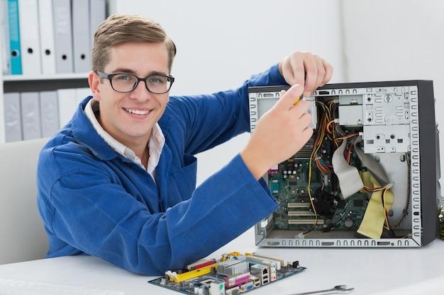 Glimlachende technicus die aan gebroken computer werkt