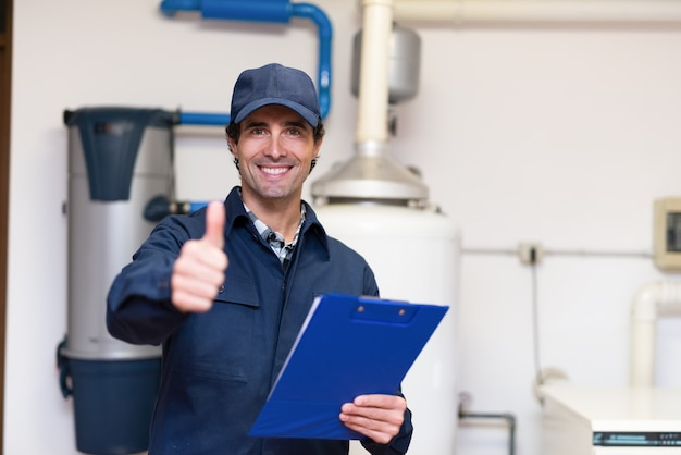 Glimlachende technicus die een warm waterverwarmer onderhouden
