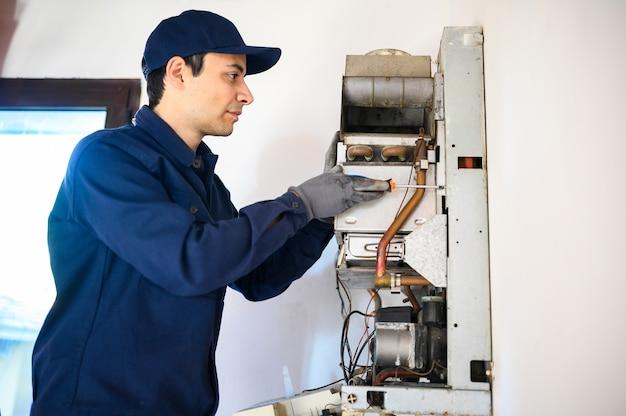 Glimlachende technicus die een warmwaterverwarmer herstelt