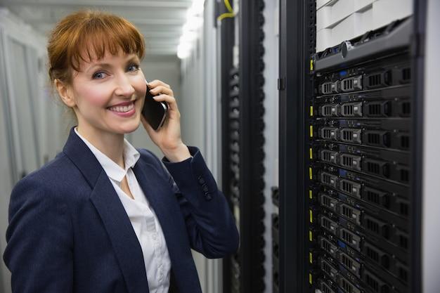 Glimlachende technicus die op telefoon spreken terwijl het bekijken server