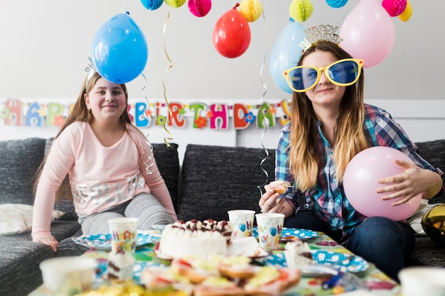 Glimlachende teenages die op verjaardagspartij eten