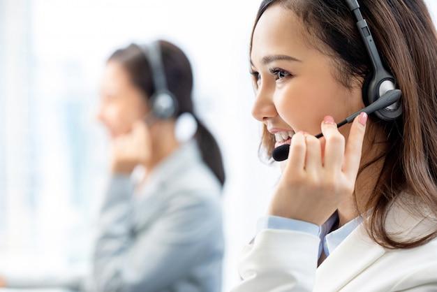 Glimlachende telemarketing aziatische vrouw die in call centrebureau werken