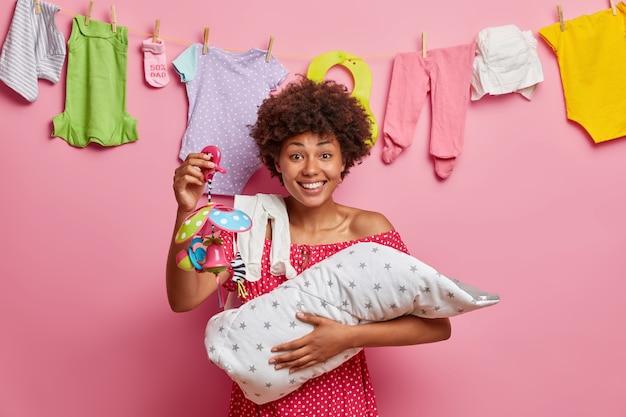 Glimlachende tevreden etnische moeder toont mobiel speelgoed aan haar kleine baby, speelt met pasgeboren zoon, blij om moeder te worden, staat binnen tegen roze muur. baby in moeders armen. kinderopvang concept.
