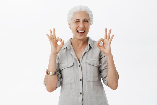 Glimlachende tevreden hogere vrouw die goed gebaar toont en knipoogt, prijs uitstekende keus
