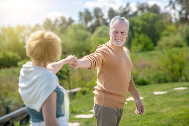 Glimlachende tevreden knappe mannelijke danser die een vrouw om een dans op het platteland vraagt