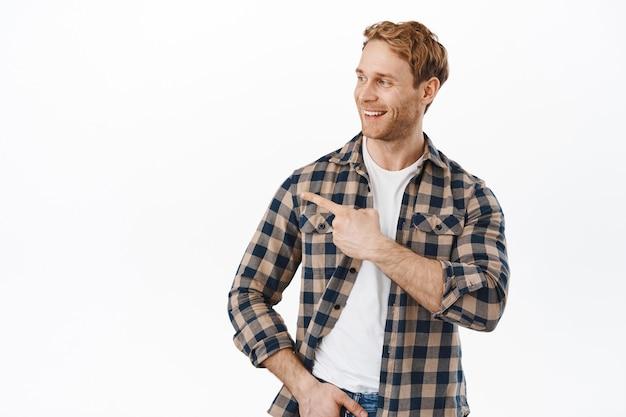 Glimlachende tevreden mannelijke klant wijzend en naar links kijkend met een blij gezicht, goedkeurend knikken, iets kiezen, promo-aanbieding tonen, tegen een witte muur staan.