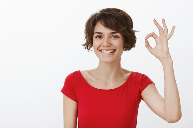 Glimlachende tevreden vrouw prijst uitstekend werk, garandeert kwaliteit of beveelt het product met een goed gebaar aan