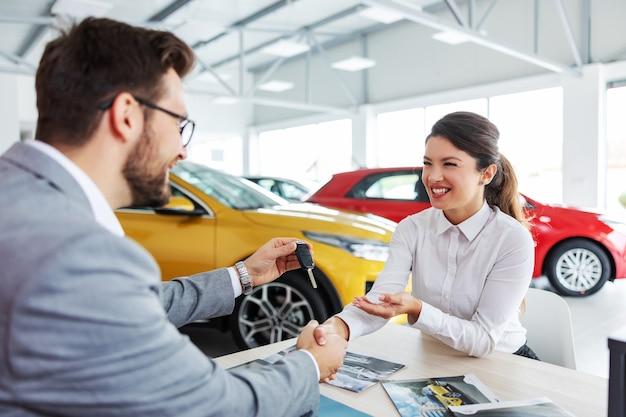 Glimlachende tevreden vrouw zittend aan de tafel met autoverkoper, hem de hand schudden en autosleutels te nemen